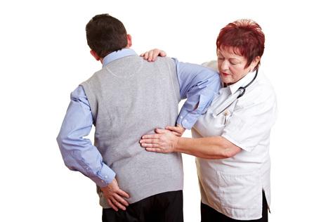 Mann mit Rückenschmerzen beim Arzt